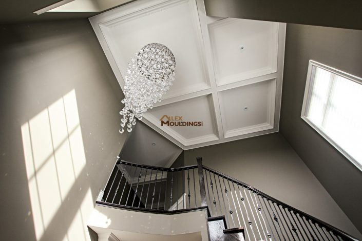 Coffered ceiling above the stair with chandalier