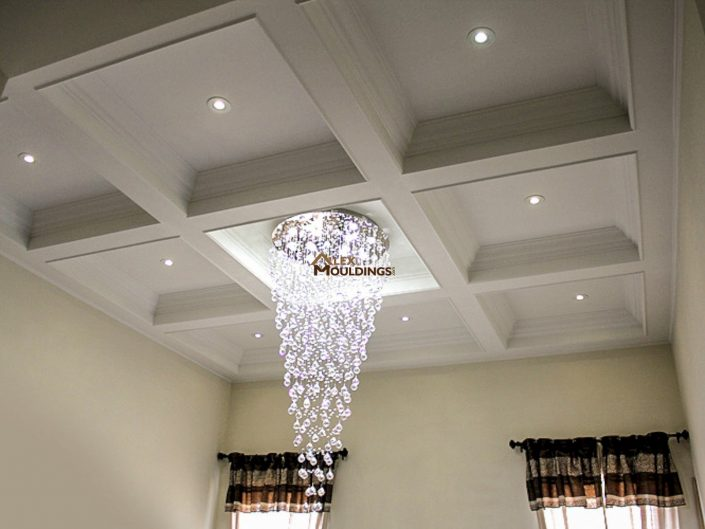Waffle ceiling with a chandelier in a middle