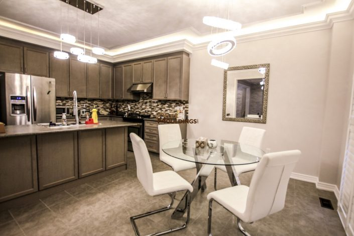 Kitchen area designed with crown mouldings and lighting