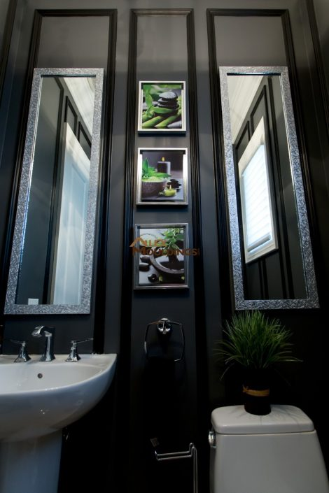 dark colour powder room decorated with pictures and wainscotting